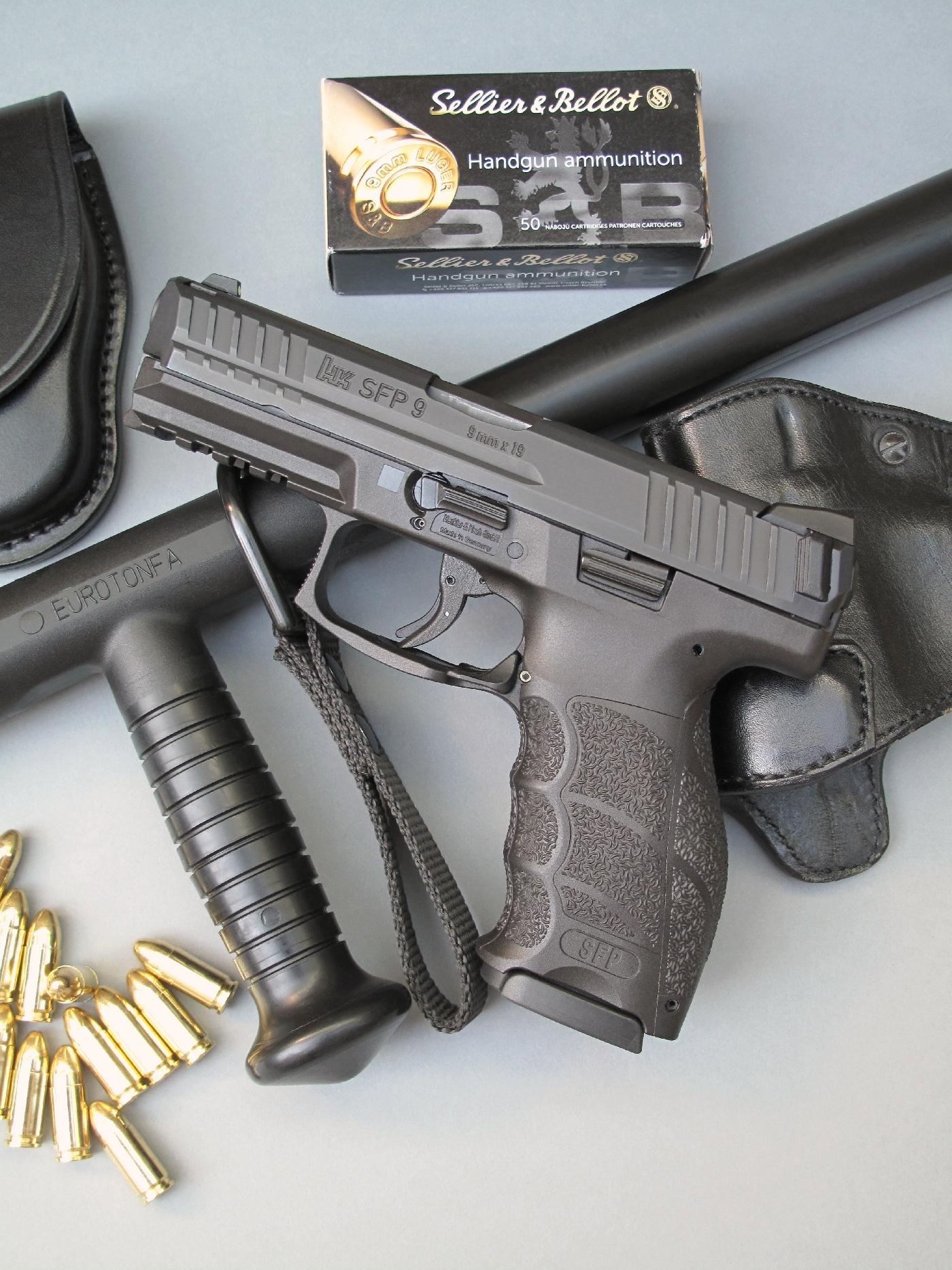 Le pistolet HK SFP 9 est accompagné ici par un holster en cuir (La Sellerie du Thymerais), un Tonfa en polypropylène (ESP) et une boîte de 50 cartouches de calibre 9 mm Parabellum manufacturées par la firme Sellier & Bellot.