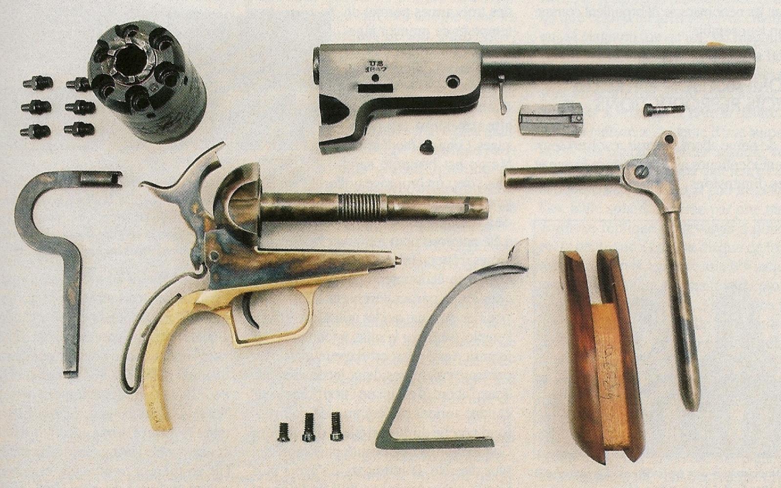 Voici le démontage que nous vous conseillons d'effectuer lorsque vous devez procéder au nettoyage de votre arme après le tir. Remarquez, sous le barillet et ses six cheminées, la présence d'une clef à cheminées qui est une copie du modèle d'époque destiné au Colt Walker. A noter que cette clef fait également office de tournevis.