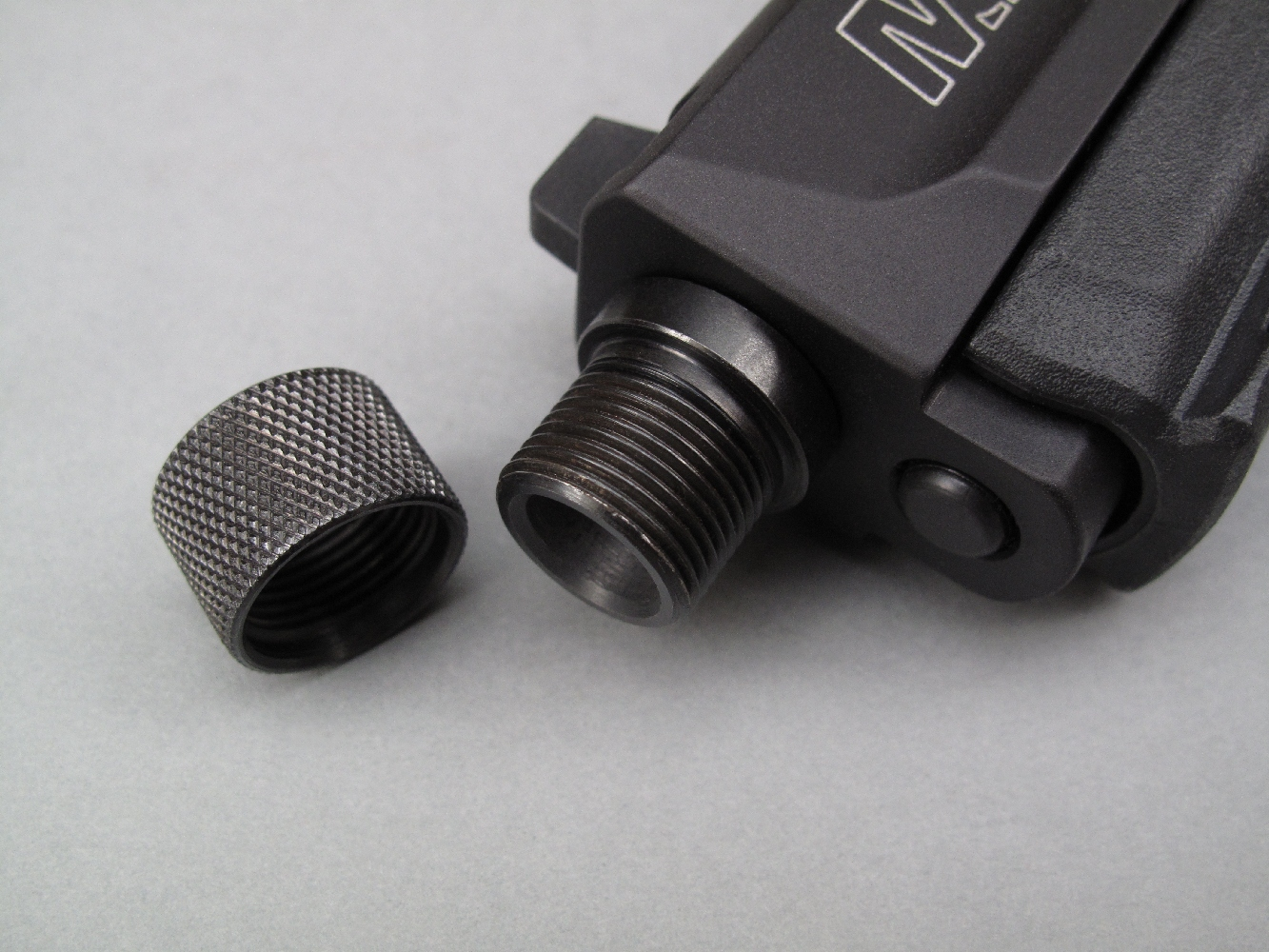 Le filetage de l'embout du canon est muni d'un bouchon de protection finement quadrillé afin de pouvoir être aisément desserré à la main.