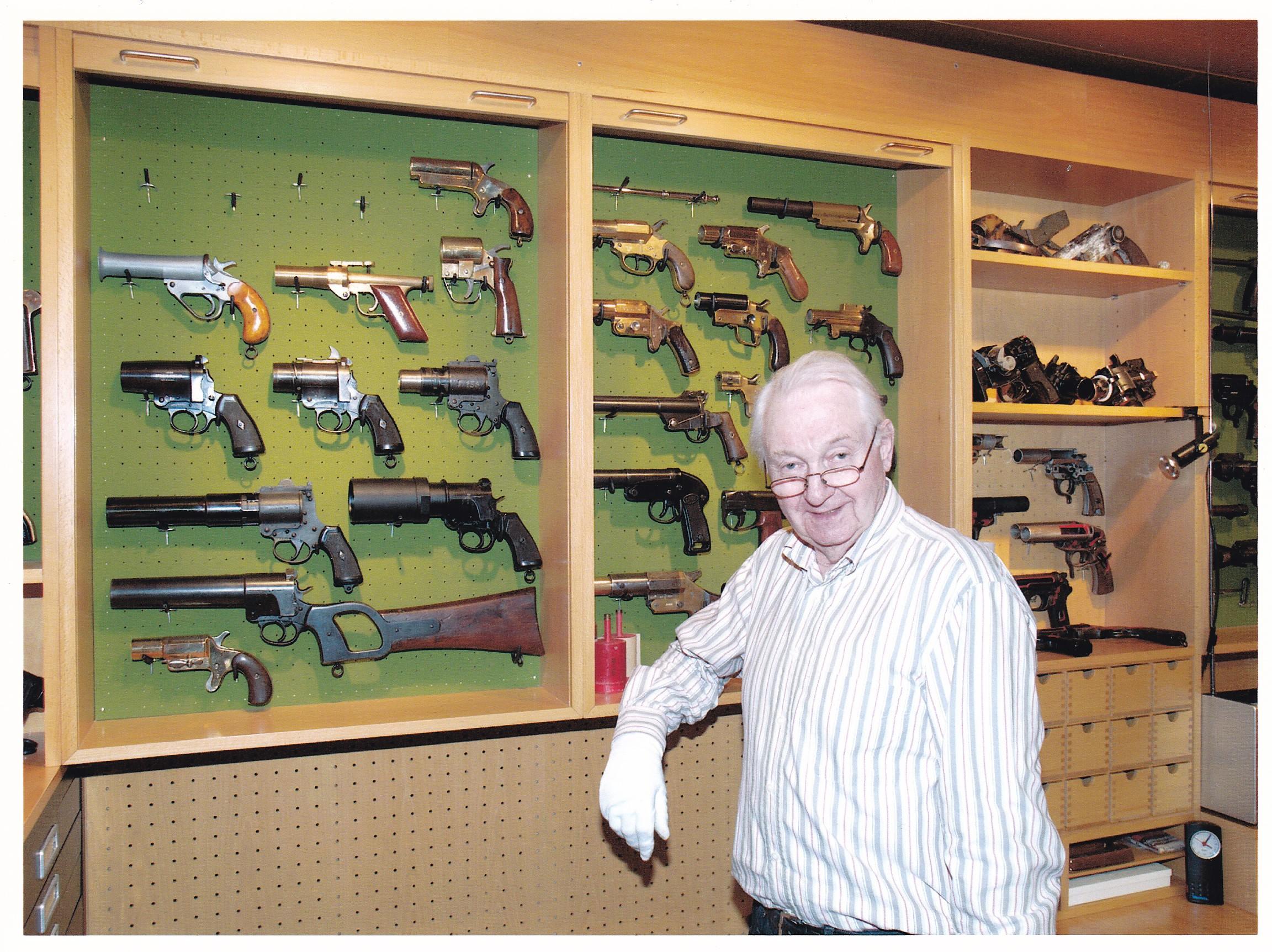 Le Dr Bruno Baumgarten photographié chez lui, dans la pièce qu'il avait à l'époque dédiée à sa collection des pistolets lance-fusées.