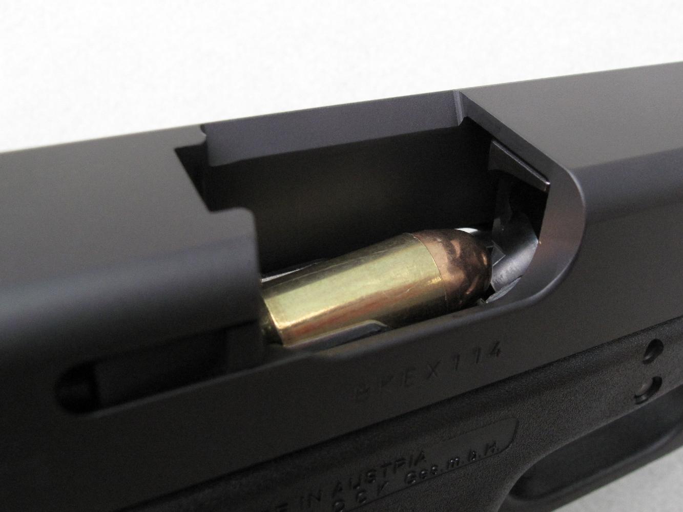 Cette vue, prise au travers de la fenêtre d'éjection, permet d'observer la grosse cartouche de calibre .45 ACP face à la rampe d'alimentation du canon.