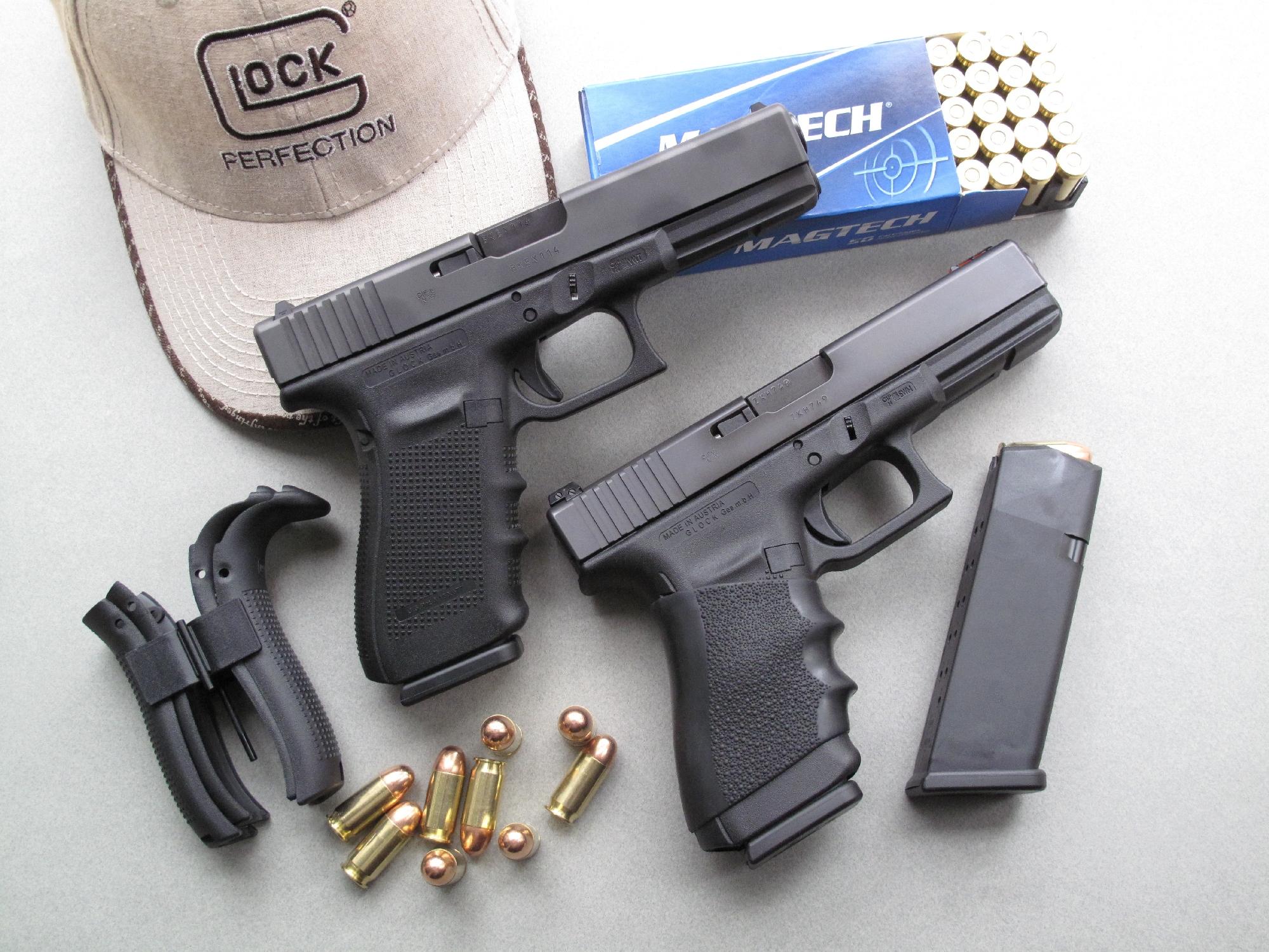 Les deux Glock 21 que nous avons utilisés pour ce banc d'essai sont accompagnés ici par une boîte de cartouches manufacturées par la firme brésilienne Magtech et par les quatre dos qui permettent, au gré de l'utilisateur, d'augmenter le volume de la poignée.