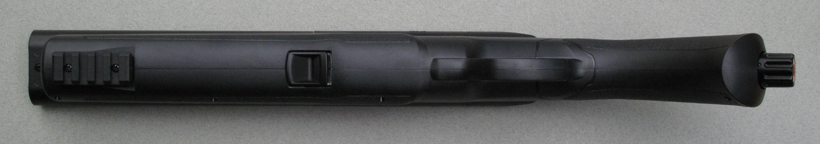 Cette vue du dessous permet d'observer, au centre du fût, le bouton qui commande l'ouverture des canons et, à l'avant, le rail Picatinny destiné à la fixation d'accessoires tactiques, comme une lampe torche ou un désignateur laser.