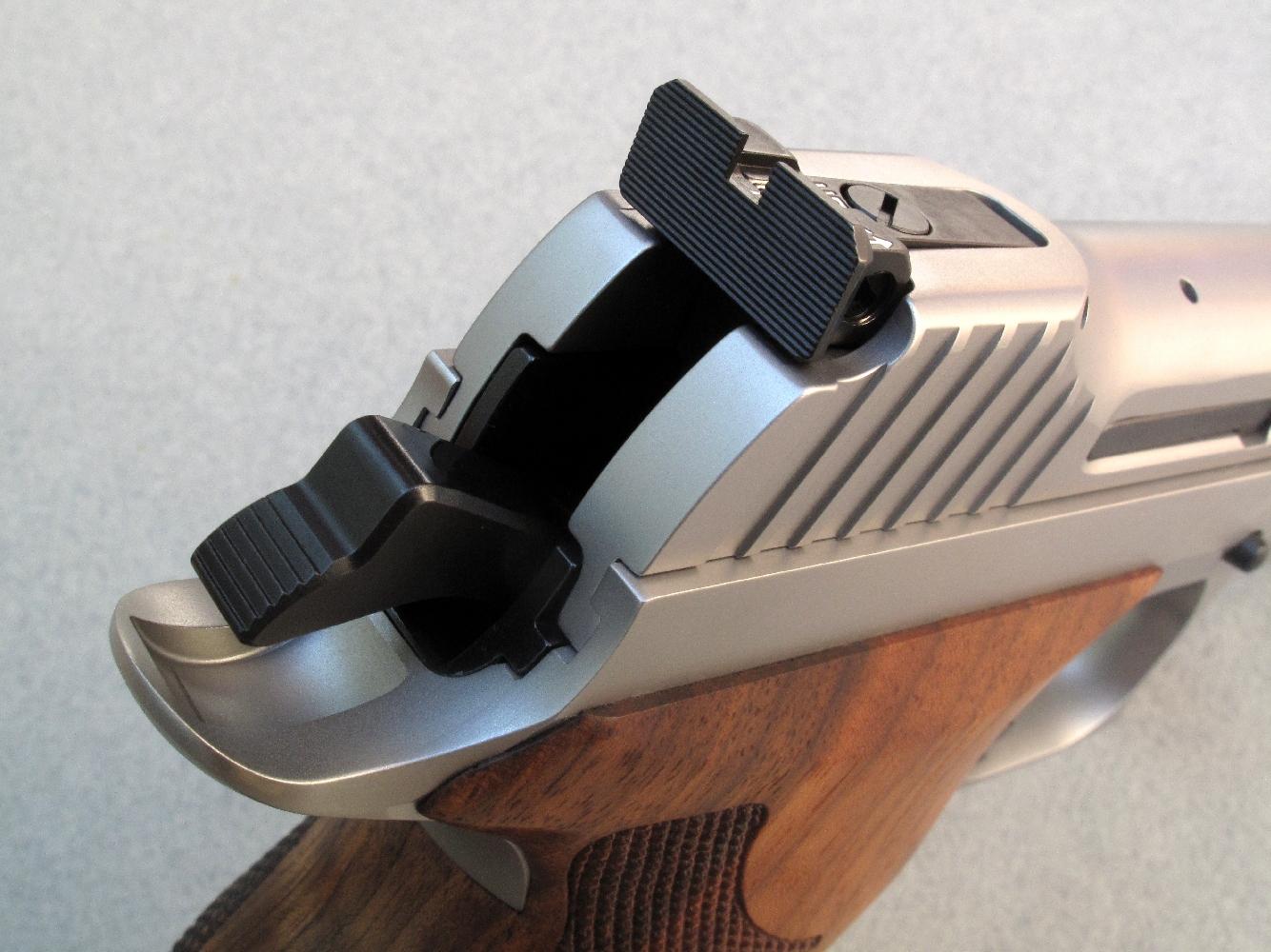 Ce pistolet dispose d'une hausse réglable, en site et en azimut, au moyen de vis micrométriques dont l'incidence est indiquée par des flèches.