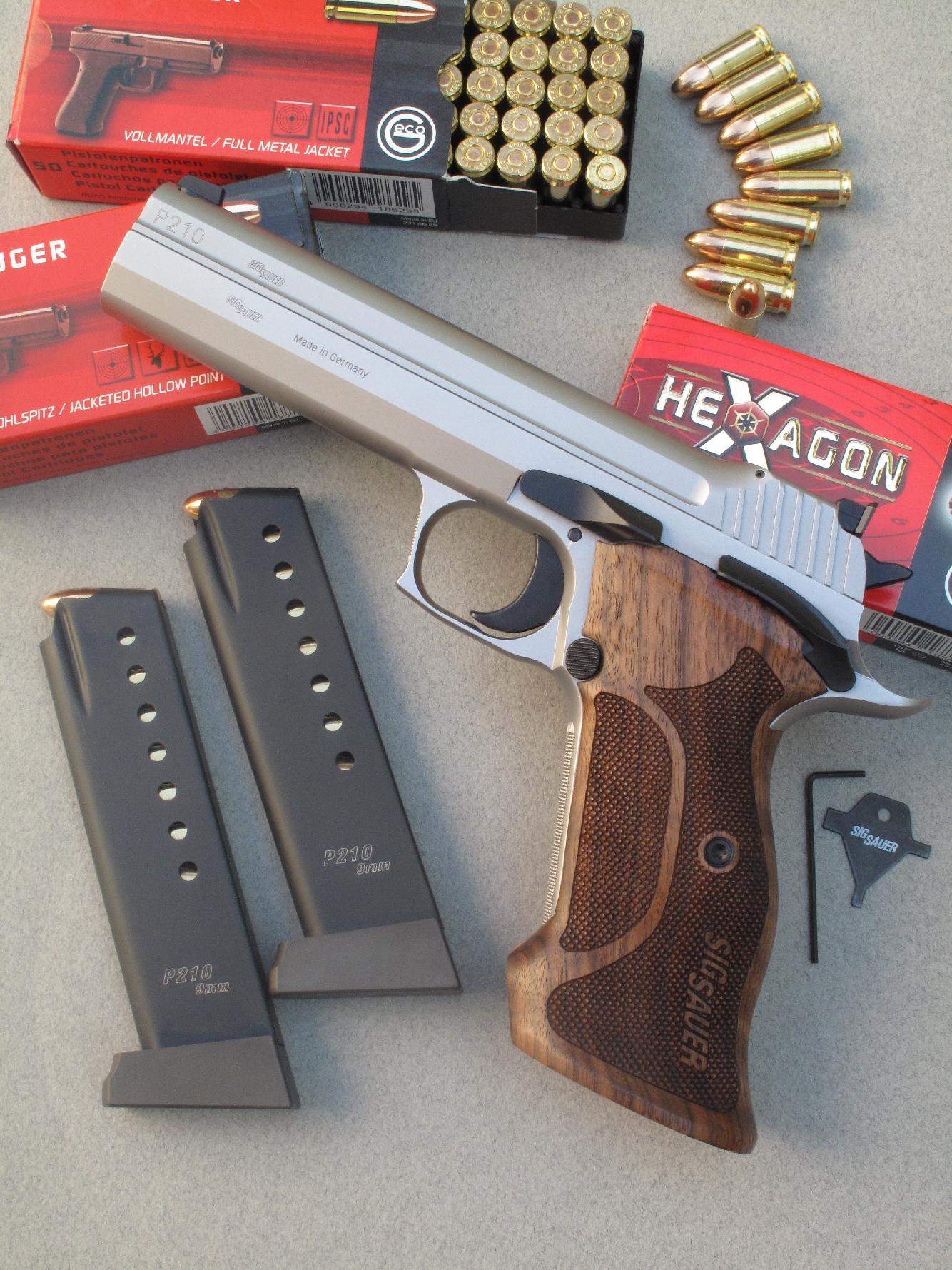 Le pistolet SIG-Sauer P210 Super Target est accompagnée ici par ses deux chargeurs de huit coups, par l'outil destiné au réglage de la hausse et par des cartouches manufacturées par la firme allemande Geco.