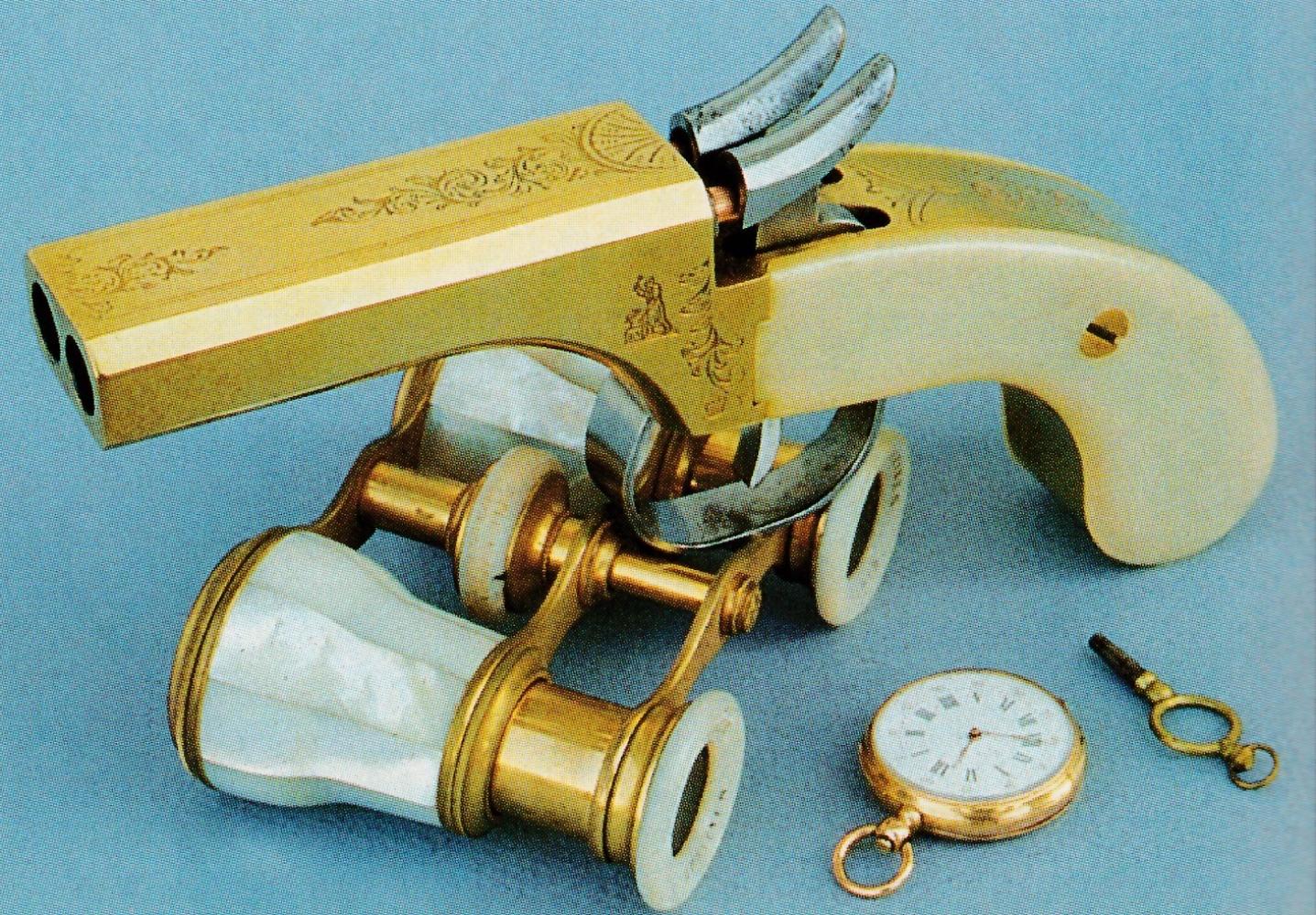 """Cette originale réplique d'un pistolet de voyage était commercialisée par la Navy Arms Company sous la dénomination de """"Snake Eyes"""" (yeux de serpent) en raison du dessin formé par la bouche de ses deux canons juxtaposés."""