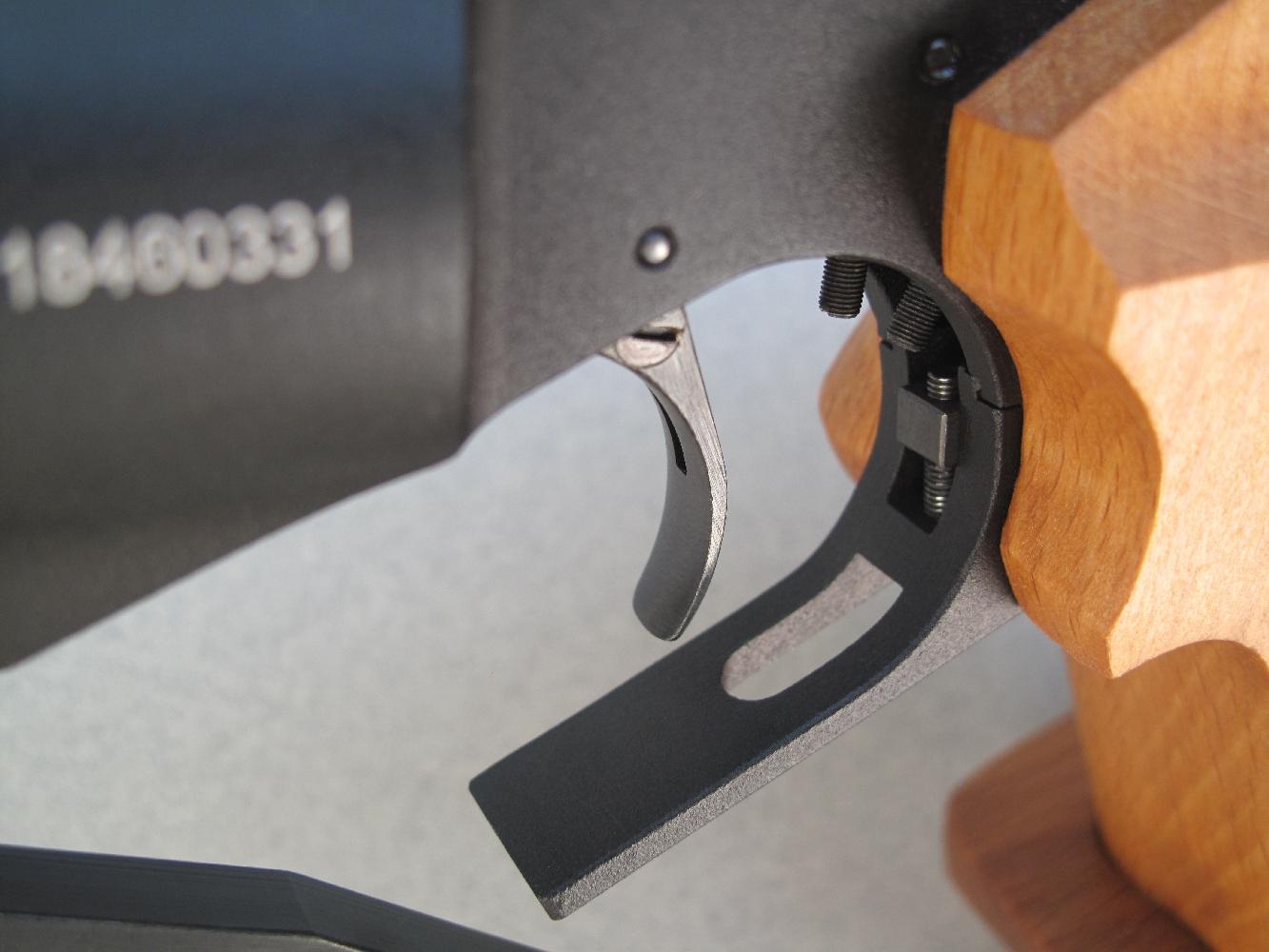 La vis située sur le côté gauche de la queue de détente permet de la bloquer sur le rail le long duquel elle coulisse.