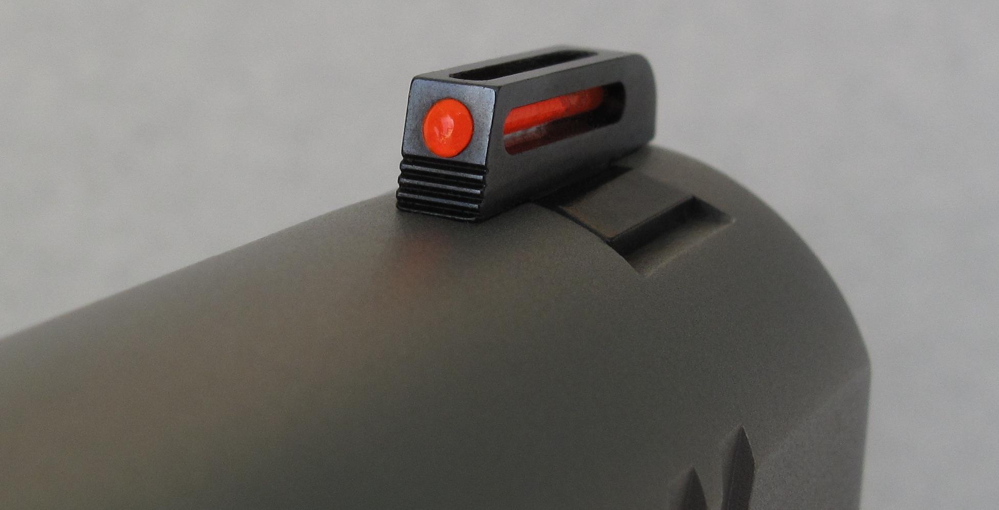 Usiné en acier et installé à queue d'aronde, le guidon intègre une fibre optique de couleur rouge.