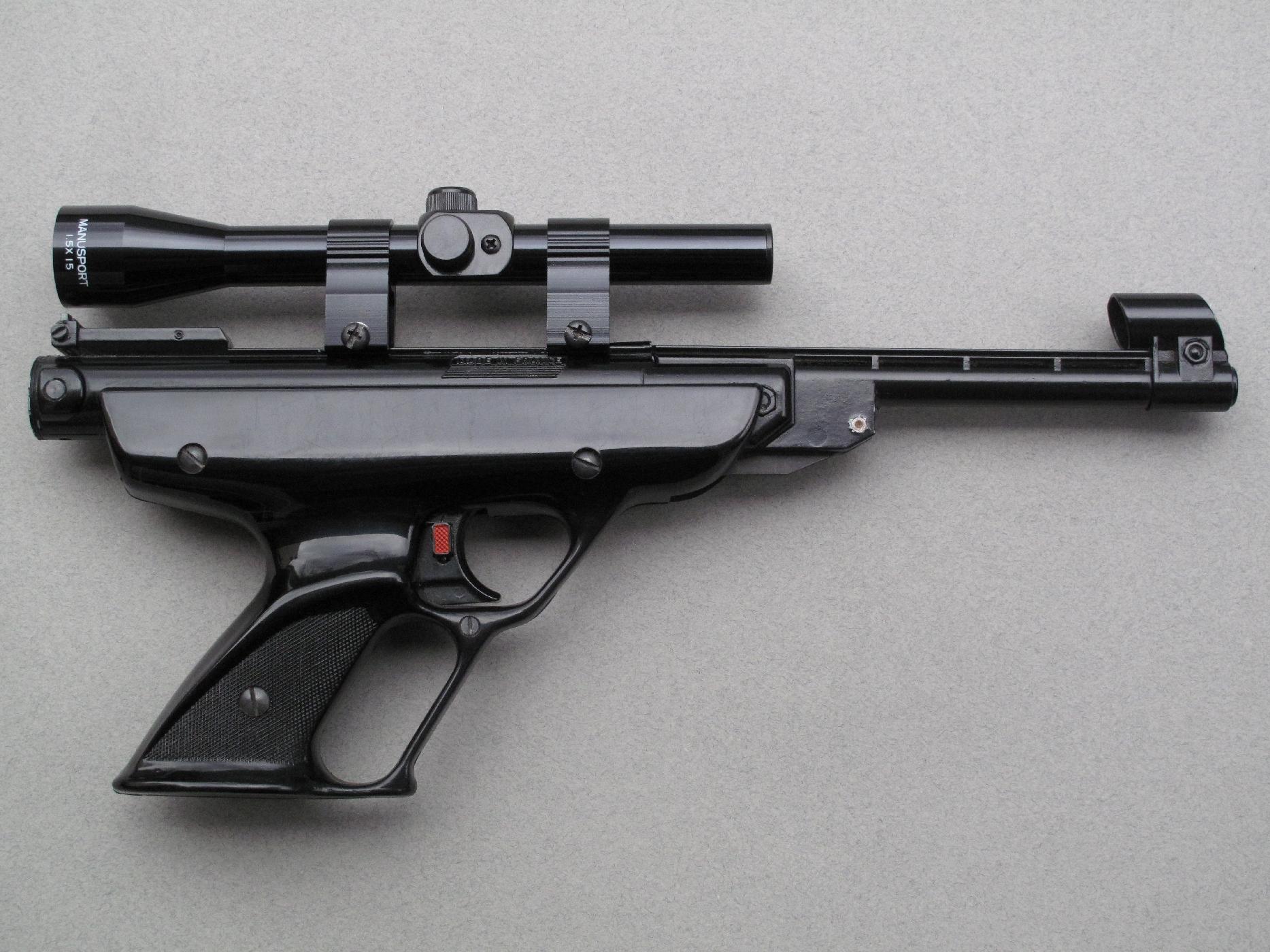 Pistolet Manu-Arm modèle Manusport dans sa livrée noire, équipé d'une lunette Manusport 1,5 x 15 dont l'œilleton est conçu pour une observation à bout de bras. On notera que l'œilleton de la lunette Manusport ne possède pas de réglage dioptrique, ce qui la rend encore plus compacte que la lunette Manu-Arm destinée elle-aussi aux armes de poing.