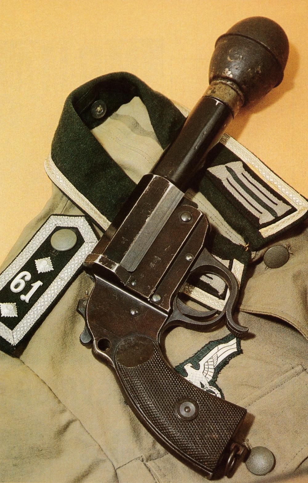 """Pistolet allemand Heer modèle 1934 de type """"Guerre"""" chargé d'un Wurfkörper 361 du 2ème type, dont le tir dans le canon lisse du pistolet signaleur ne nécessite pas l'emploi d'un manchon de renfort. Cette munition est constituée par une grenade """"œuf"""" fixée sur un tube de lancement."""