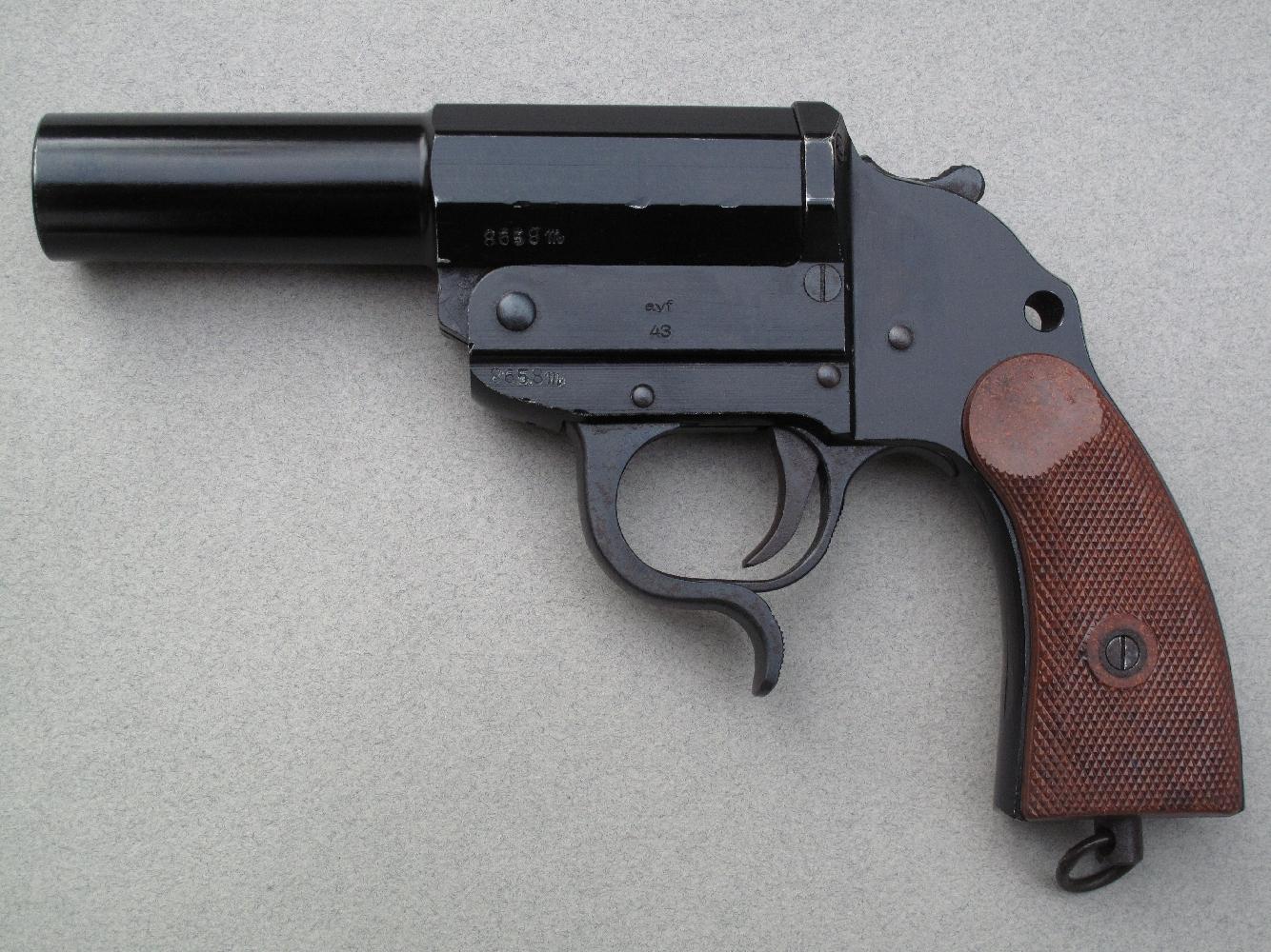 """Pistolet signaleur Heer modèle 1934 type """"Guerre"""" (Gazette des Armes N°508) fabriqué par ERMA (code de guerre """"ayf"""") en 1943. Il se démarque notamment par la présence d'un témoin de chargement, situé sur le côté gauche du rempart."""