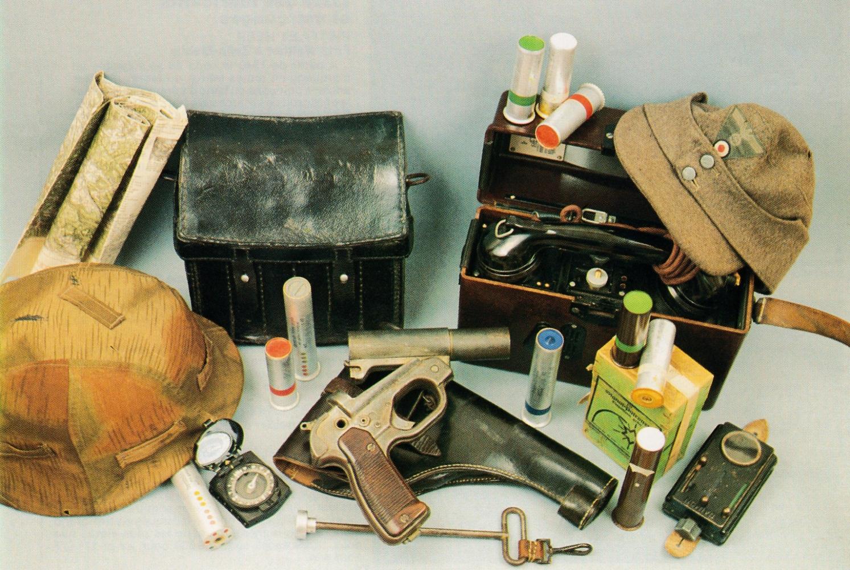 Pistolet signaleur allemand modèle LP 42 (1942) accompagné de son étui de transport, sa baguette de nettoyage et une sacoche en cuir pouvant recevoir 18 cartouches de calibre 4. Il est présenté dans un environnement évoquant les transmissions, avec notamment un appareil téléphonique modèle 1933.
