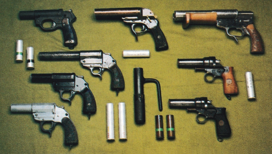 """Divers pistolets lance-fusées allemands, de gauche à droite et de haut en bas : Modèle LP42 ; Modèle """"L"""" d'aviation ; Walther SLd à double-canon ; Walther modèle 1926 ; VZ-30 de la firme tchèque CZ daté de 1933 ; Heer modèle 1934 ; lanceur à main utilisé dans les casemates ; Heer modèle 1934 en zink ; VZ-30 fabriqué pour les Allemands daté de 1939."""