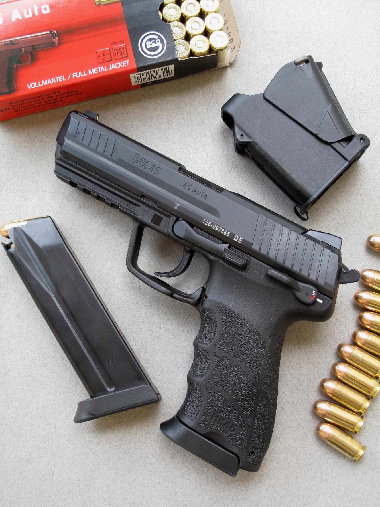 Le pistolet HK 45, accompagné par son chargeur de secours, une boîte de munitions manufacturées par la firme allemande Geco et l'outil d'aide au chargement universel UpLULA commercialisé par firme israélienne Maglula.