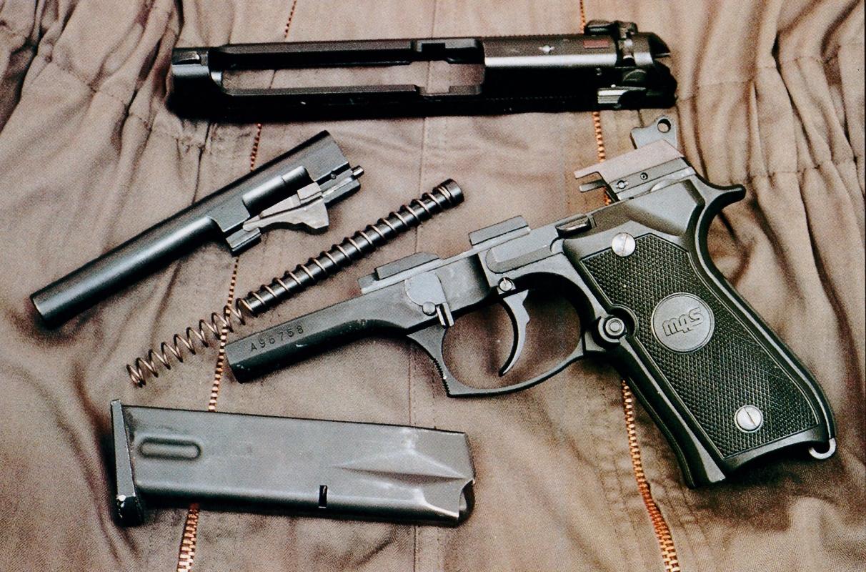 – La sécurisation de l'arme est obtenue au moyen d'un disque solidaire de l'axe du chien et d'une rainure fraisée dans la partie postérieure de la glissière.